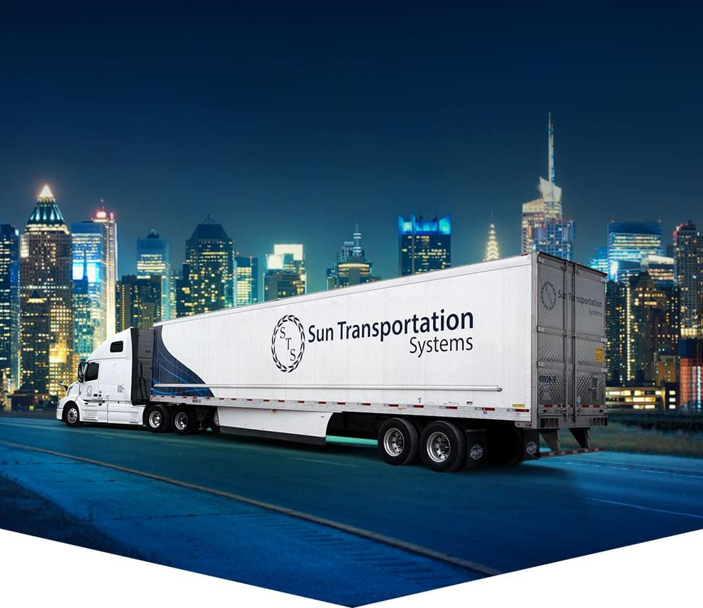 Sun Transportation Systems transport truck driving on highway into a USA city.