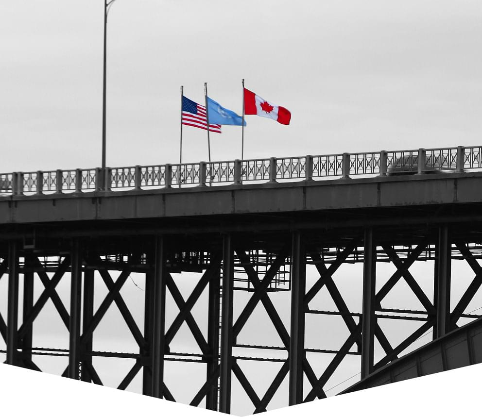 A border bridge crossing, with Canadian and American flags flying.